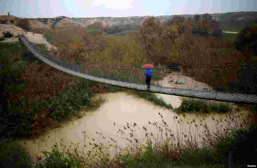 A man walks on a bridge crossing over a stream near a Kibbutz in Israel's southern Negev desert. (Reuters/Amir Cohen)