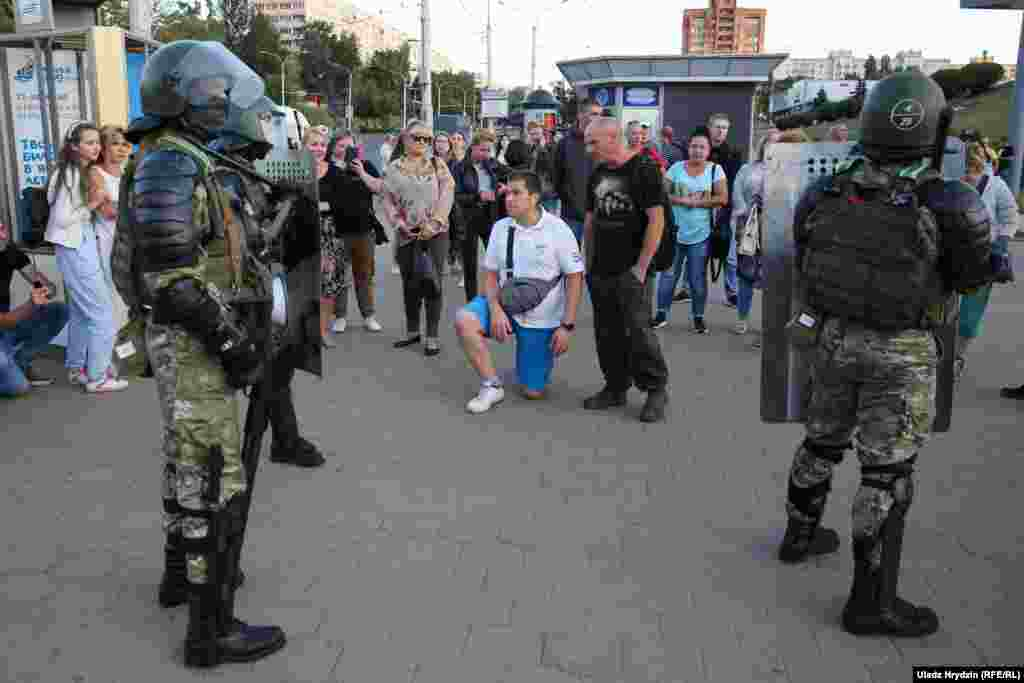 Security forces in riot gear stand near the site where a protester died in Minsk.
