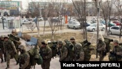 """Вооруженное и по-зимнему экипированное подразделение внутренних войск направляется в здание """"Казахтелекома"""" с тыльной стороны. Актау, 21 декабря 2011 года."""