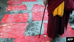 Tibetan Buddhist monk in exile walks over Chinese national flags as part of a protest in Dharamsala in March 2008.