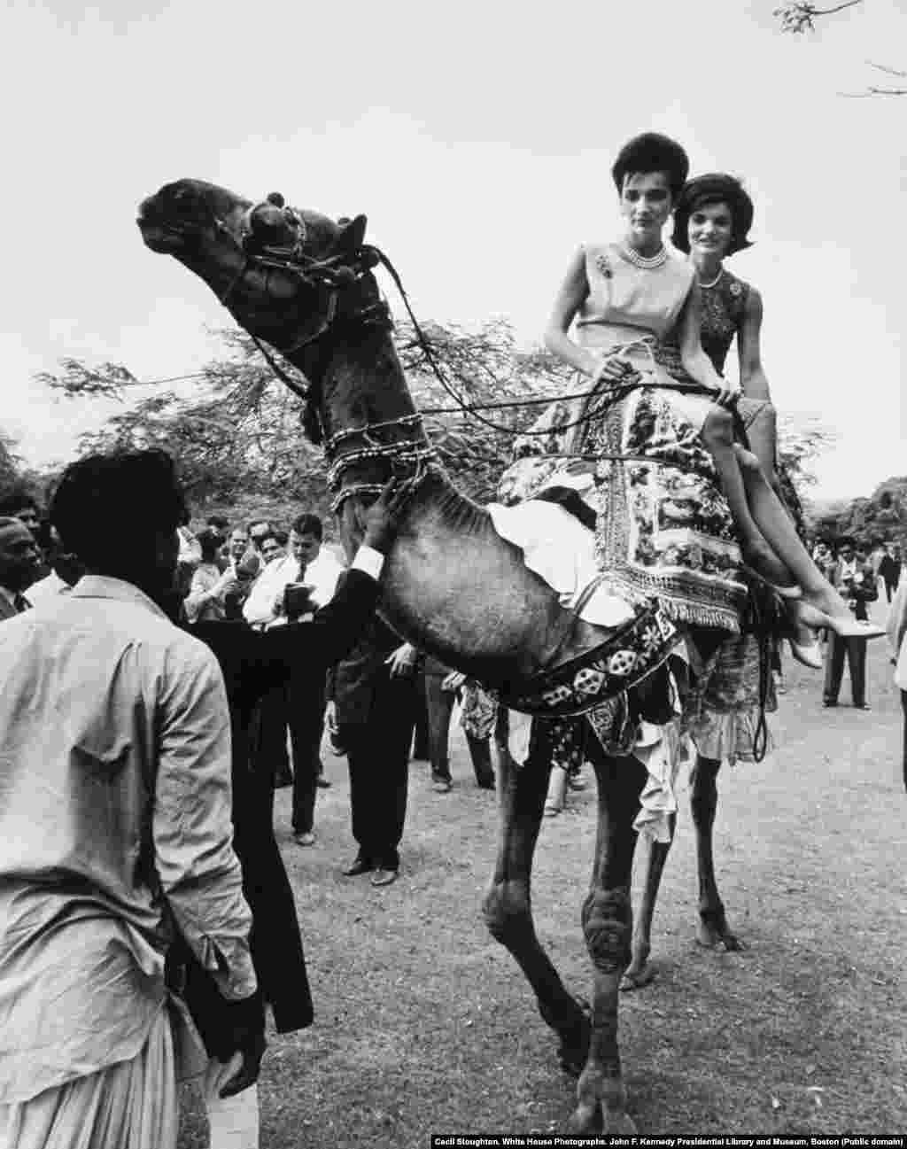 Жаклин Кеннеди (справа) и Ли Радзивилл верхом на верблюде Ахмада. На видео, запечатлевшем момент, первая леди и ее сестра, сидя на лежащем верблюде, просят погонщика, чтобы верблюд встал на ноги. Резко взглянув на американок, Ахмад Башир приказал ревущему верблюду подняться, после чего сестры совершили небольшую прогулку верхом.
