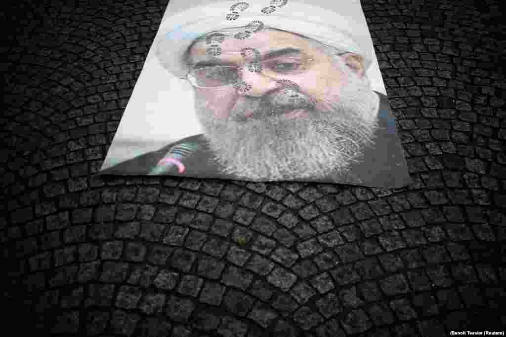 A portrait of Iran's President Hassan Rohani lays on a street as thousands of Iranian opponents in exile staged a protest in Paris against the Tehran regime, before the 40th anniversary of the Islamic Revolution. (Reuters/Benoit Tessier)