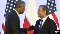 Then-Polish Prime Minister Donald Tusk (right) shakes hands with U.S. President Barack Obama following a meeting in Warsaw in June 2014.