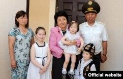 Роза Отунбаева фотографируется с семьей офицера в День Армии. 28 мая 2011 года.