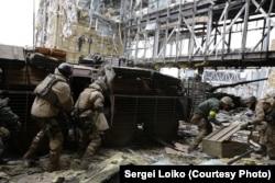 «Киборги» (украинские солдаты, защищающие донецкий аэропорт) под обстрелом забирают тело танкиста, Донецк, 19 октября 2014 года