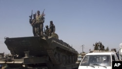 Syrian soldiers stand on their armored vehicle in Hama on August 10.
