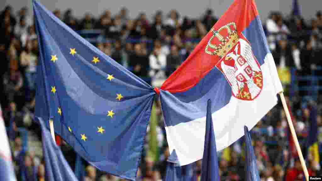 Tadic supporters wave Serbian and EU flags at a May 17 rally. Tadic says a third term would be dedicated to European integration and economic development. (REUTERS/Ivan Milutinovic)