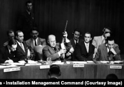 "Warren Austin, a U.S. delegate to the United Nations, holds a Soviet-made PPSh submachine gun, known as a ""burp gun."" Captured by U.S. troops in Korea, it was displayed as evidence that Stalin was backing the invasion by communist forces."