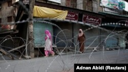 Kashmiri women walk past concertina wire laid across a road during restrictions after the scrapping of the special constitutional status for Kashmir by the Indian government in Srinagar on August 20.