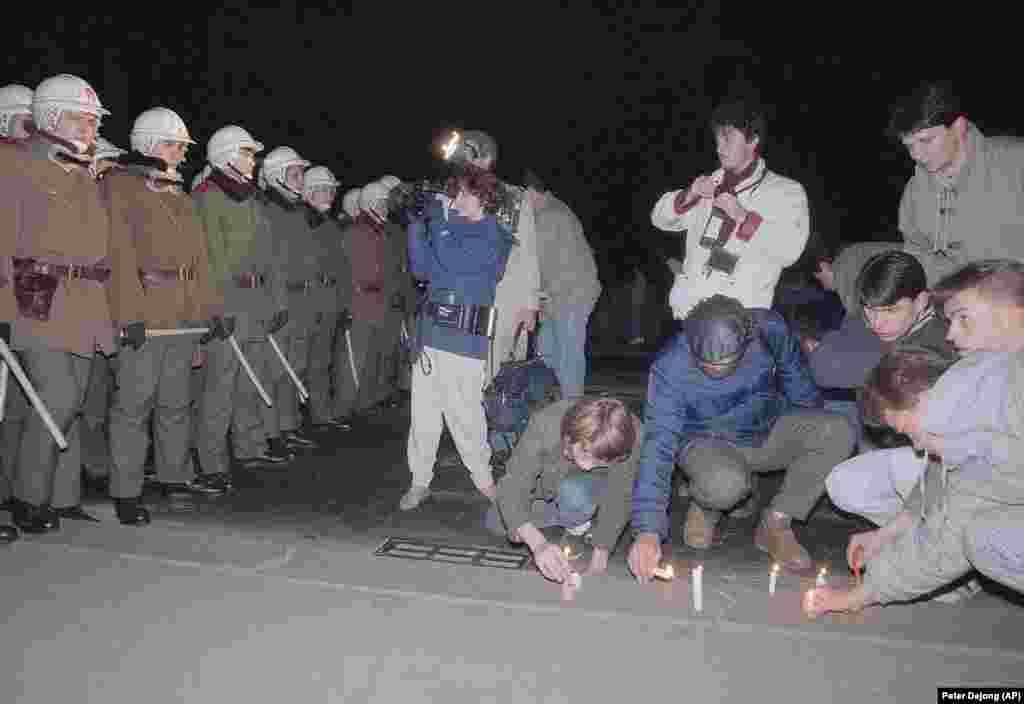 Протестующие зажигают свечи у полицейского кордона, который не дал им перейти мост, 21 ноября.