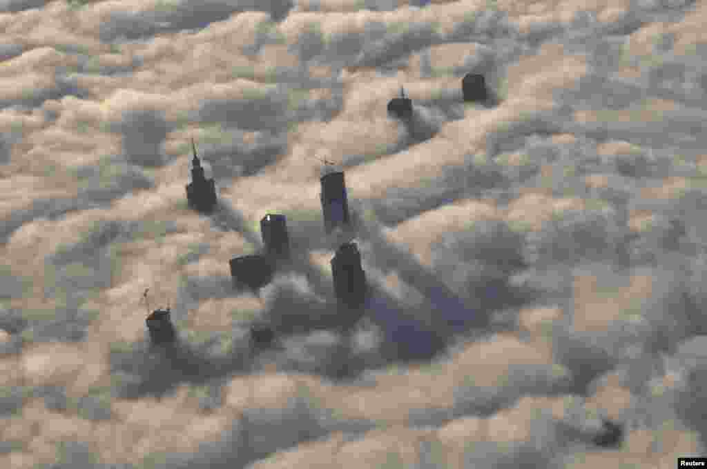 The tops of high-rise buildings stick out from a blanket of thick fog covering Warsaw early one morning. (Reuters/Mateusz Olszowy)