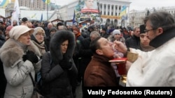 Ukrainians receive sacrament during a gathering organized by supporters of EU integration at Maidan Nezalezhnosti, or Independence Square, in central Kyiv on December 8, with organizers hoping 1 million people will turn out to show their anger over the administration's U-turn on the EU.