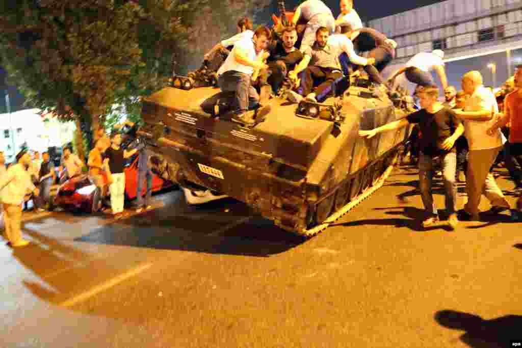 A tank, crowded with civilians, drives over two cars in Istanbul in the early hours of July 16.