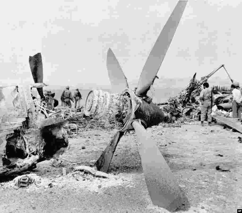 The wreckage of a burned-out American C-130 Hercules cargo plane is inspected by Iranian troops in the Dasht-e Kavir desert, some 500 kilometers from Tehran, on April 26, 1980. An RH-53 helicopter collided with the plane during the attempt to free the American hostages. Mechanical problems and a sandstorm hampered the mission, and a U.S. commander advised Carter to abort. The accident happened after the abort order was given. The helicopter's rotor churned up sand, blocking visibility. Carter put much of the blame for his loss in the 1980 presidential election on his failure to free the hostages.