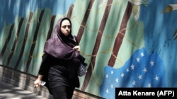 A woman walks by a mural on the wall of the former U.S. Embassy in Tehran in August 2018.