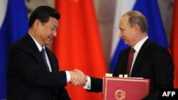 Russian President Vladimir Putin (right) meets with his Chinese counterpart Xi Jinping in Moscow.