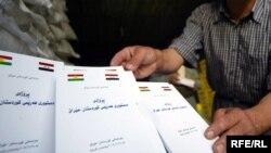 رجل يعرض نسخاً من مسودة دستور إقليم كردستان