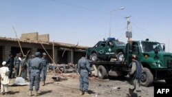Police officers and security officials clear the debris after a suicide blast in Lashkar Gah, which killed five people.
