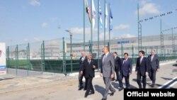 Владелец Baghlan Group Хафиз Маммадов и сын министра транспорта Азербайджана Анар Маммадов в сопровождении подчиненных показывают президенту Ильхаму Алиеву территорию автопарка, куда были доставлены такси из Лондона.