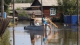 RUSSIA -- Local residents sail a boat in the flood-hit settlement of Oktyabrsky in Irkutsk Region, Russia July 5, 2019.