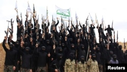 Islamist fighters hold up their weapons during their graduation ceremony at a camp in Syria, near Damascus, in November 2013.