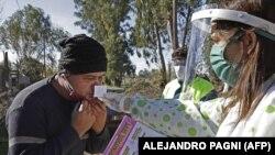 Zdravstveni radnik radi olfaktorni test - praćenje rada osjeta mirisa - stanovniku u naselju Altos de San Lorenzo, u blizini grada La Plata, 65 km od Buenos Airesa, 7 juni 2020.