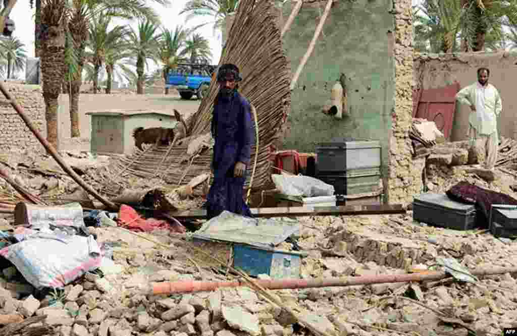 Residents look through the debris of a house, which collapsed after the earthquake hit the Awaran district in Balochistan Province.