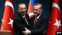 Turkey -- Azerbaijani President Ilham Aliyev (L) and Turkish President Recep Tayyip Erdogan hug after signing bilateral agreements following the 5th Turkey-Azerbaijan High Level Strategic Cooperation Council meeting at the Presidential Complex in Ankara,
