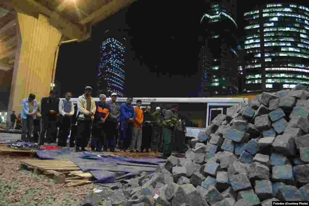 Tajik workers pray at a construction site. Moscow, 2007. Photo by Julia Vishnevetskaya.