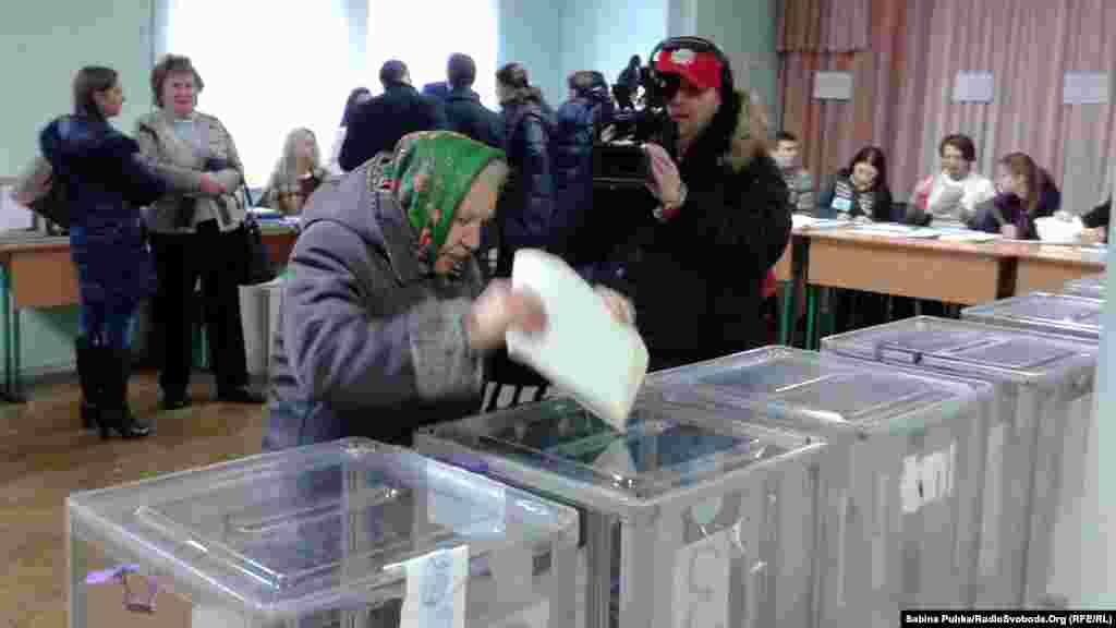 Пожилая женщина бросет бюллетень в урну для голосования. Киев, 26 октября 2014 года.
