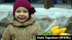 Kazakhstan - Girl with flowers on the eve of International women's day /screen shot/. Almaty, 07Mar2012.