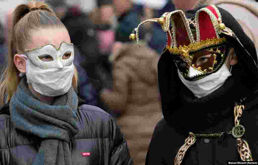 Туристы надевают карнавальные маски вместе с защитными