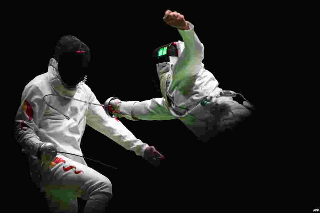China's Jiao Yunlong (L) competes against Ukraine's Bogdan Nikishin during their men's individual epee qualifying bout as part of the fencing competition.
