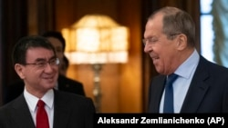 Russian Foreign Minister Sergei Lavrov (right) and Japanese Foreign Minister Taro Kono enter a hall for their talks in Moscow on January 14.