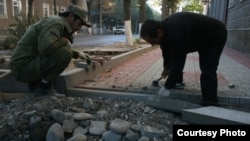 Two men repair a sidewalk in Tskhinvali, in South Ossetia.