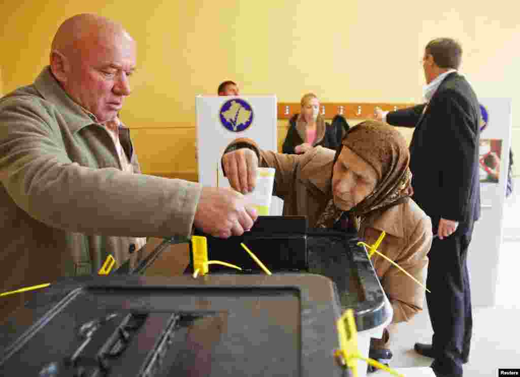 A Kosovar Albanian man and woman vote in Mitrovica.