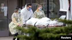 کادر یک آسایشگاه سالمندان در تورنتوی کانادا در حال بیرون بردن جسد یکی از ساکنان این آسایشگاه