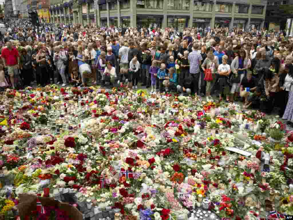 Mourners crowd around a floral tribute in the Norwegian capital, Oslo, to the victims of the July 22 bomb explosion that ripped through government buildings and a related shooting spree at a political youth camp. Photo by Odd Andersen for AFP