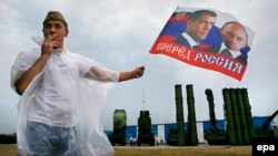 A man holds a flag with portraits of Russian President Vladimir Putin and Prime Minister Dmitry Medvedev in front of S-300 surface-to-air missile systems during a military exhibition outside Moscow in 2014.
