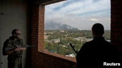 Pro-Russian rebels watch from a building as smoke rises near the Donetsk airport after recent shelling on September 23.