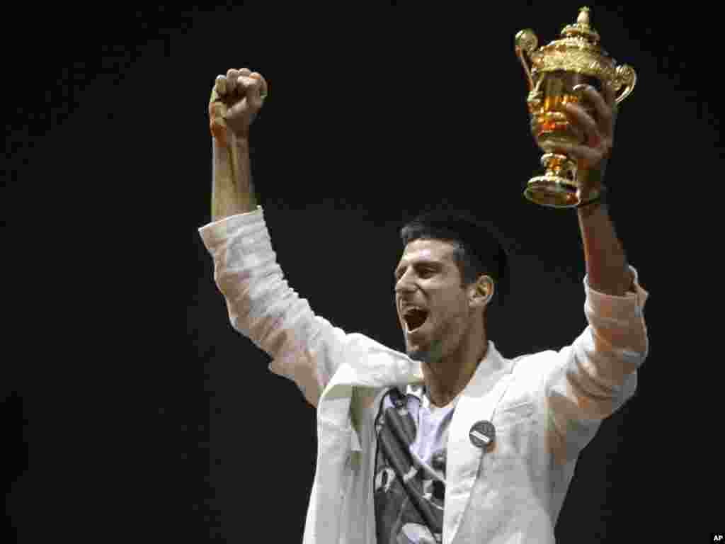 Tennis player Novak Djokovic reacts as he lifts up the Wimbledon men's singles trophy in Belgrade. Djokovic received a rapturous welcome in Serbia following his triumph at Wimbledon and on his first day as the world's top-ranked tennis player.Photo by Marko Drobnjakovic for The AP
