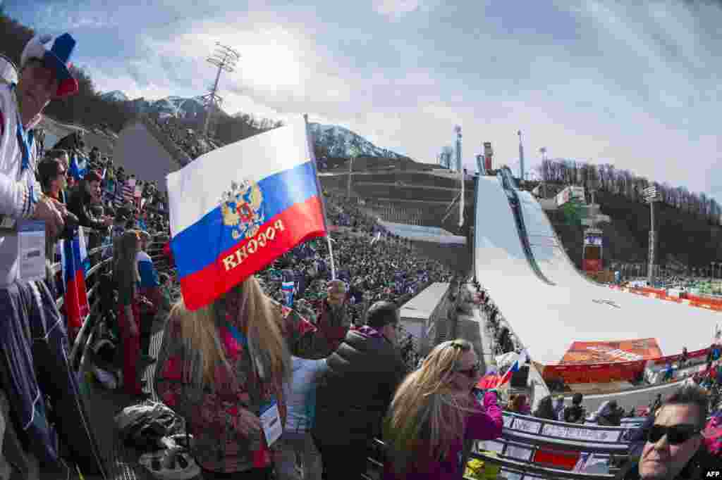 Russian nordic-combined fans wave flags during the individual competition at the RusSki Gorki Jumping Center.