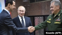 Syrian President Bashar al-Assad (left) greets Russian President Vladimir Putin (center) and Russian Defense Minister Sergei Shoigu at the headquarters of the Russian armed forces in Damascus on January 7, 2020.