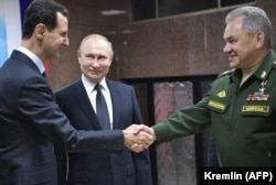 Putin (center), Syrian President Bashar al-Assad (left) and Russian Defense Minister Sergei Shoigu visit the headquarters of Russian forces in Damascus on January 7.