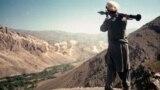 Боец наблюдава съветска бомбардировка в долина в Афганистан. През 1978 г. Афганистан преживява кървав комунистически преврат, който година по-късно е последван от инвазия от страна на СССР.