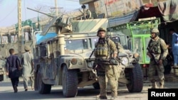 Afghan security forces keep watch in front of their armored vehicle in Kunduz city on October 4.