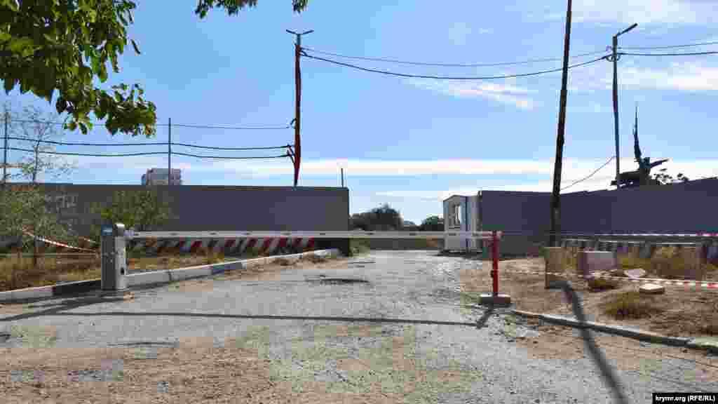Территория строительства ограждена забором, перед въездом установлен шлагбаум