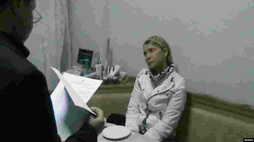 Tymoshenko is served with legal papers outlining new accusations against her by Kachanivska Prison Director Ihor Karpaschikov in her hospital room in Kharkiv in January 2013.