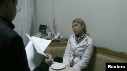 Бывший осужденный премьер-министр Украины Юлия Тимошенко заслушивает уведомление в своей больничной палате. Харьков, 18 января 2013 года.