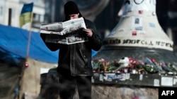 Мужчина читает газету рядом с палаточным лагерем демонстрантов на Майдане Незалежности. Киев, 24 февраля 2014 года.
